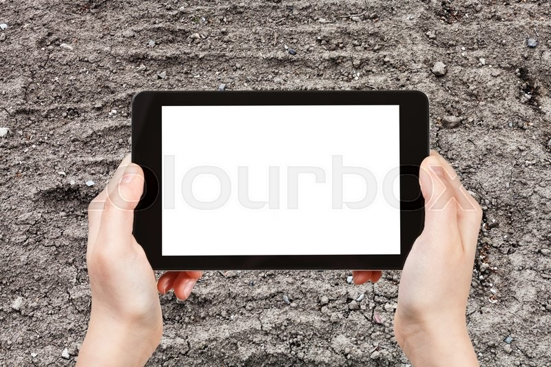 Stock image of 'gardening concept - farmer photographs empty garden ground in spring on tablet pc with cut out screen with blank place for advertising'
