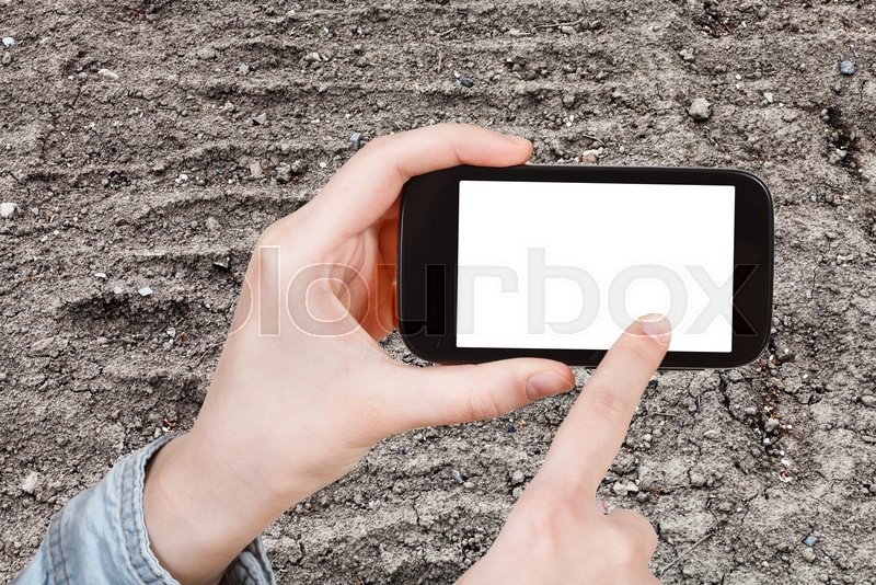 Stock image of 'gardening concept - farmer photographs plowed garden ground in spring on smartphone with cut out screen with blank place for advertising'