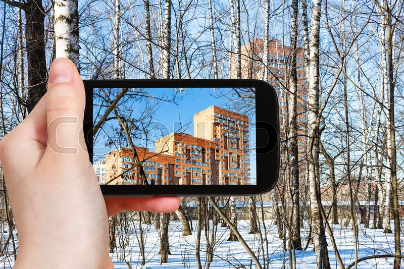 Stock image of 'season concept - tourist photographs apartment house through birch trees in spring forest on smartphone'