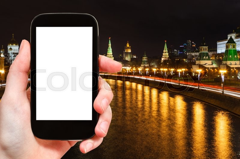 Stock image of 'travel concept - tourist photographs Moscow night landscape with Kremlin and Moskva River on smartphone with cut out screen with blank place for advertising, Russia'