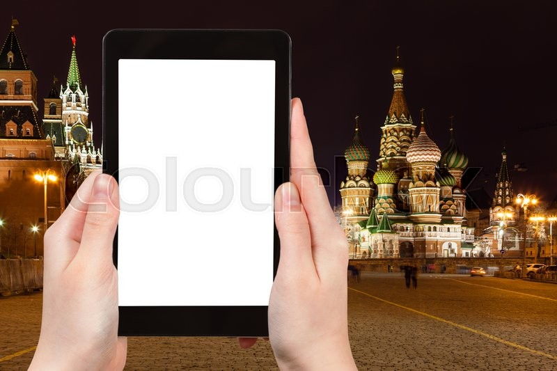Stock image of 'travel concept - tourist photographs Moscow night landscape with Kremlin Cathedral, Vasilevskiy Descent of Red Square on tablet PC with cut out screen with blank place for advertising, Russia'