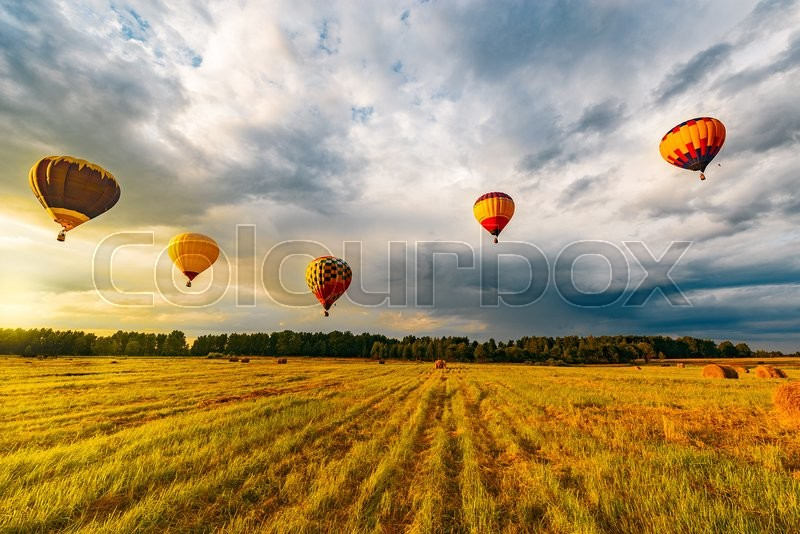 Stock image of 'Morning flight of the hot air balloons above the countryside. '