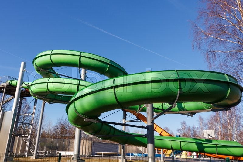 Stock image of 'An outdoors water attraction park with a green waterslide'