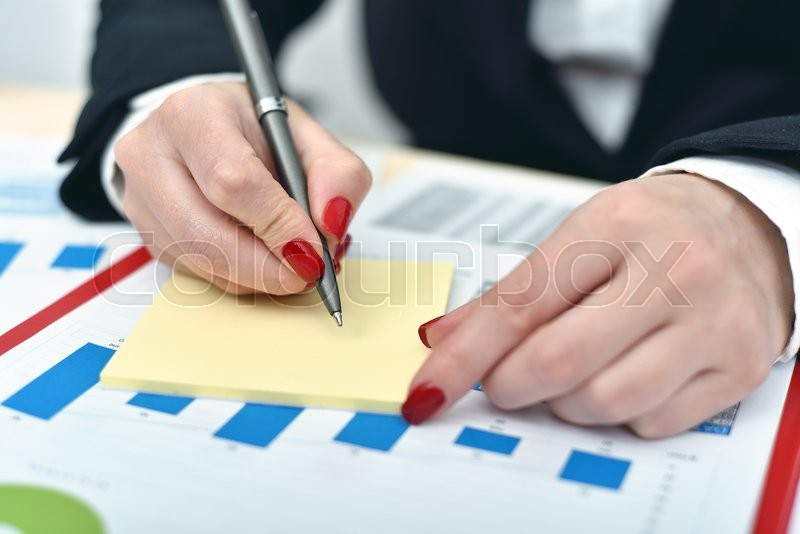Stock image of 'trader woman taking notes on a sheet of paper'