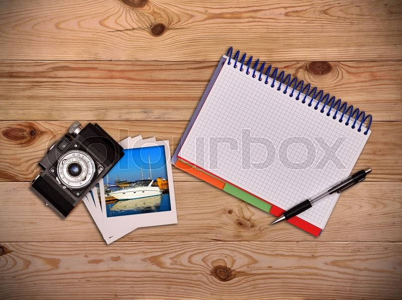 Stock image of 'Work desk tourist. Camera, photo and blank notepad with pen'