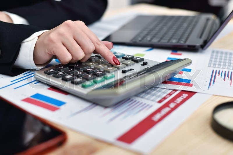 Stock image of 'accountant woman considers on the calculator profit'
