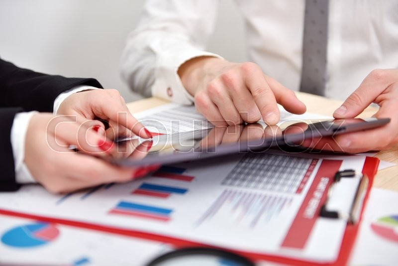 Stock image of 'businesspeople consider business growth graph on the tablet'