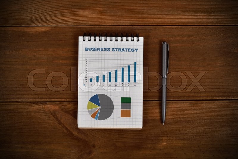 Stock image of 'note pad with drawing business stgrategy and pen on wooden table'