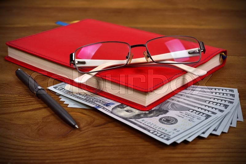 Stock image of 'red leather diary, glasses, pen and dollar bills on wooden desk'