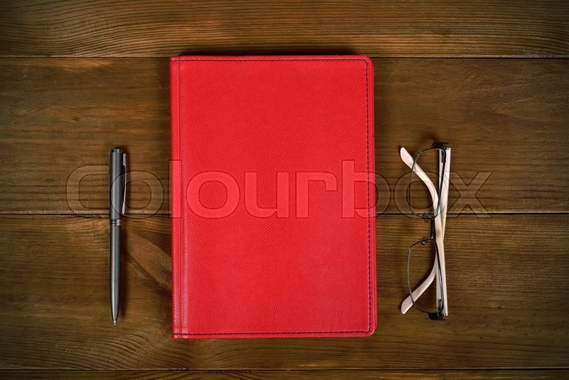 Stock image of 'top view blank red leather diary, glasses and pen on wooden desk'
