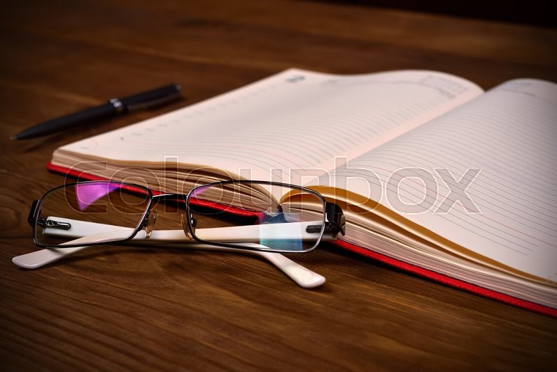 Stock image of 'open red diary, glasses and pen on wooden table, close up'