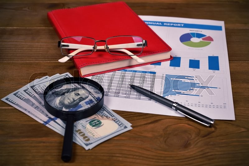 Stock image of 'Annual report, glasses, dollars and pen on table'