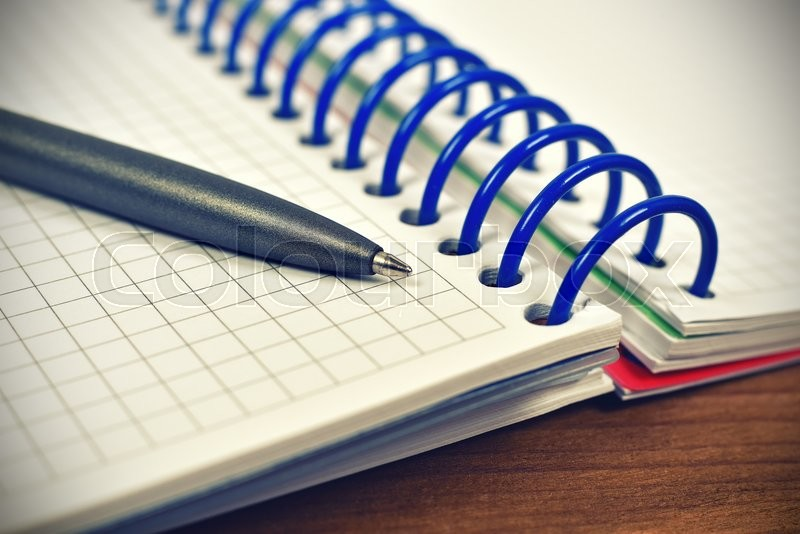 Stock image of 'note pad with pen on wooden table, close up'