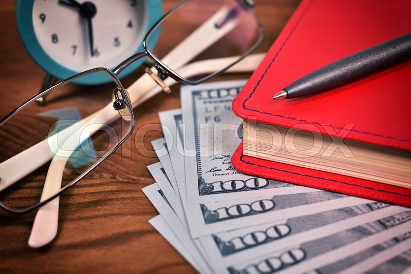 Stock image of 'red diary, glasses, pen, dollar and clock on wooden desk'