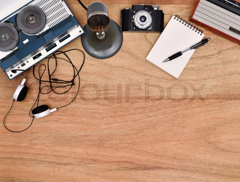 Stock image of 'Old retro reel tape recorder, vintage radio, retro camera on wooden table. Blank notepad and pen.'