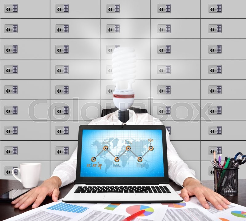 Stock image of 'Businessman with head lamp sitting in office. Start up concept on screen laptop'