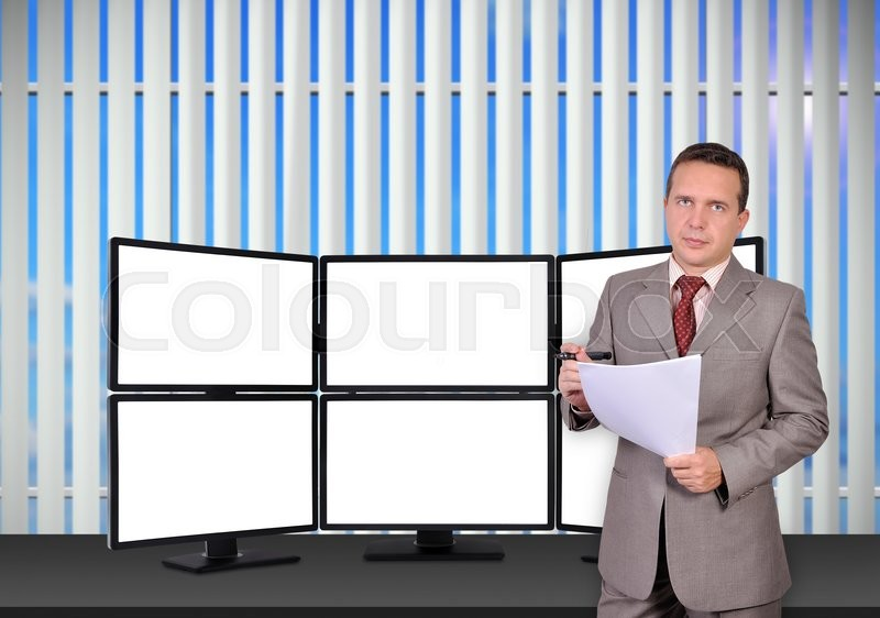 Stock image of 'trader with paper standing near trading station which consists of six blank screens'