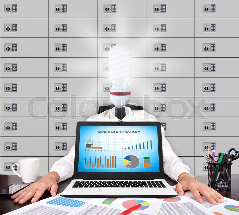 Stock image of 'Businessman with head lamp sitting in office. Business strategy concept on screen laptop'