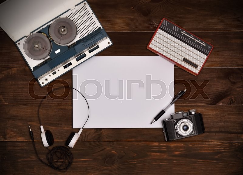 Stock image of 'Reel tape recorder with headphones, vintage radio, retro camera on wooden table. Plank paper. View from above'