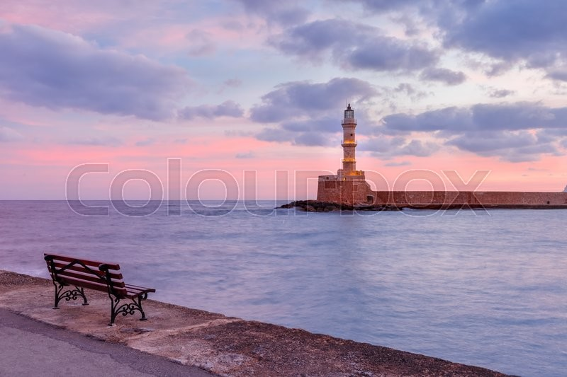 Stock image of 'Lighthouse in old harbour of Chania at sunrise, Crete, Greece'