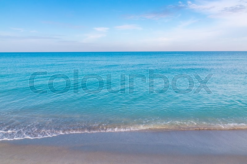 Stock image of 'Ocean, sandy beach and blue sky at early morning'