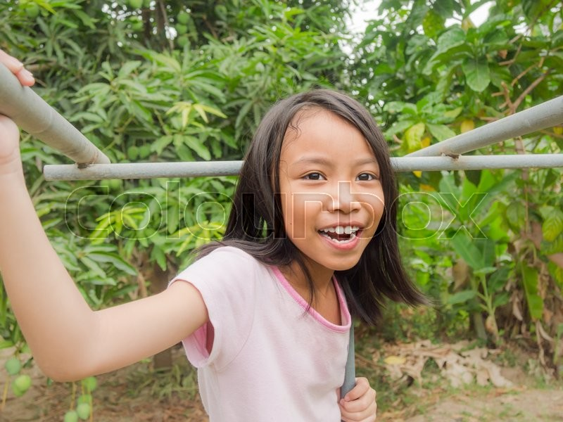 Stock image of 'Happy little asian kid  hanging on gymnastic wall on the playground'