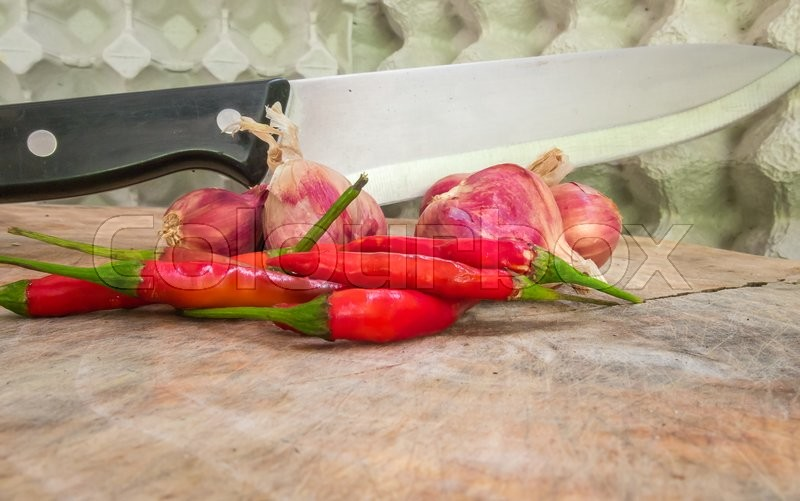 Stock image of 'Red peppers, onions on a cutting board with a knife stuck.'