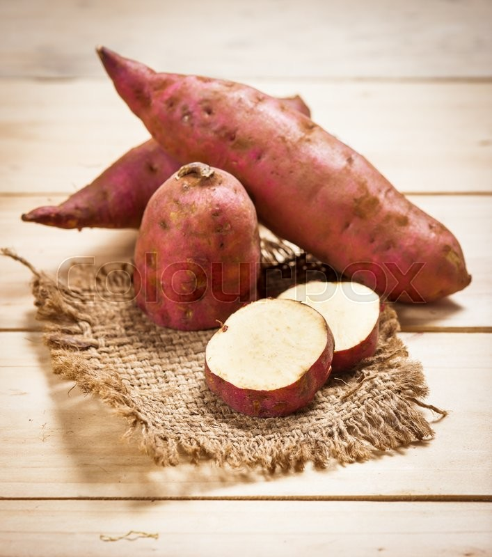 Stock image of 'Raw sweet potatoes on a wooden background . Selective focus'
