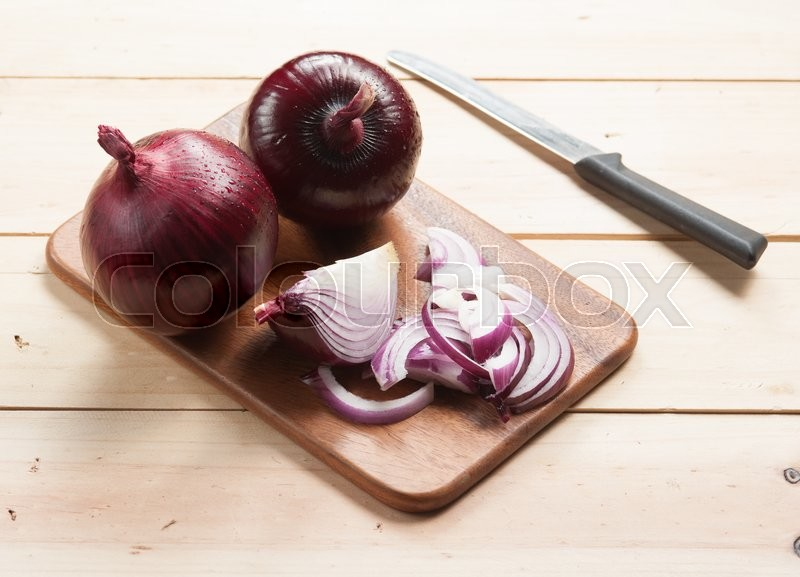 Stock image of 'Red onion and cutting board on wooden table, selective focus'