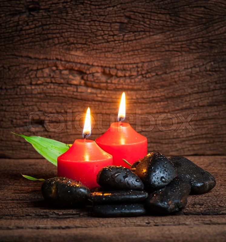 Stock image of 'Red candle and black stones on wood background'