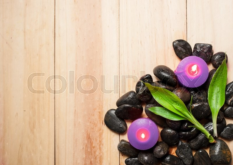 Stock image of 'Lavender candle and black stones on wood background'