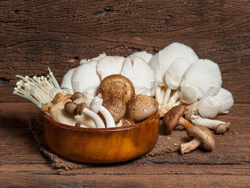 Stock image of 'Variety of Mushrooms in a basket on wood'