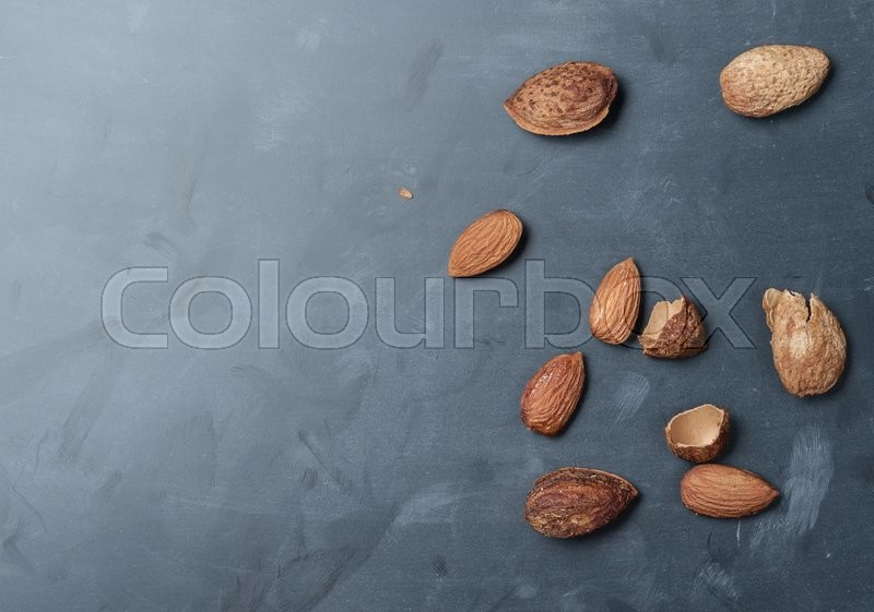 Stock image of 'Almonds on a black slate background,top view'