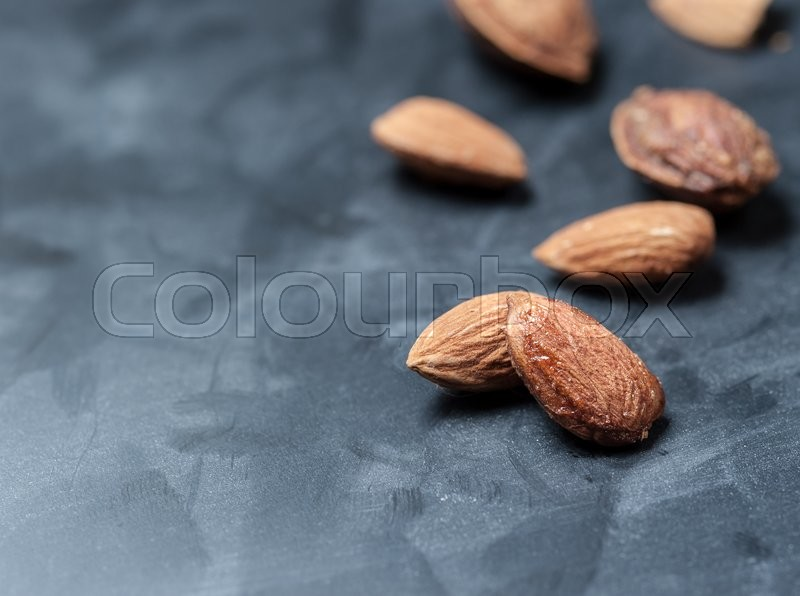 Stock image of 'Almonds on a black slate background, shallow focus'