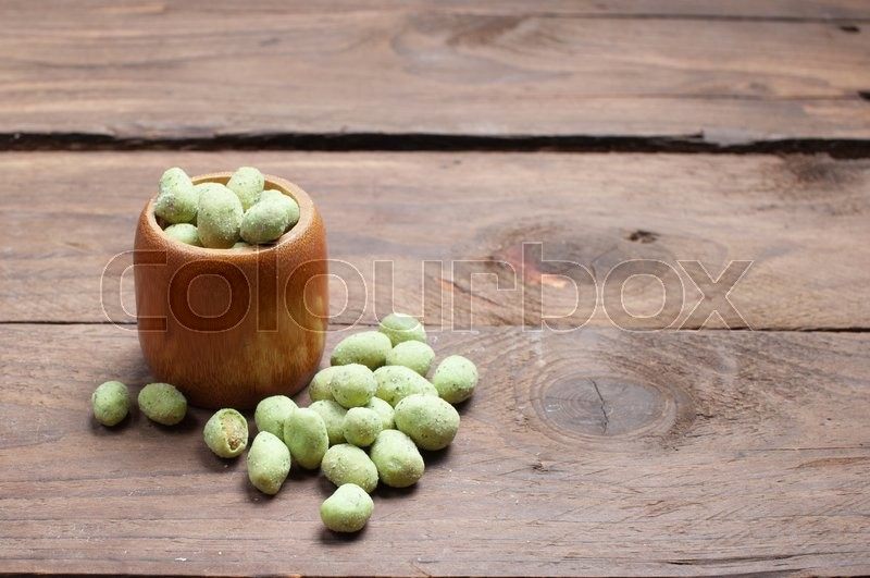 Stock image of 'Green nut on wood'