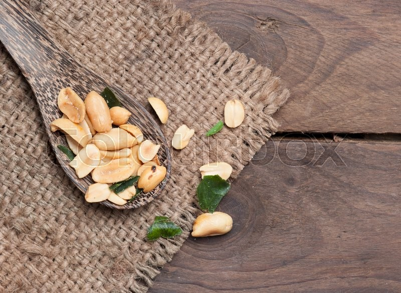 Stock image of 'Roasted Peanuts and herb on wood'