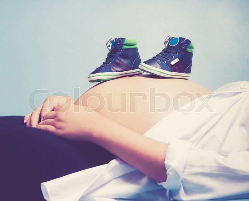 Stock image of 'Pregnant woman with baby shoe on the stomach,vintage color toned image'