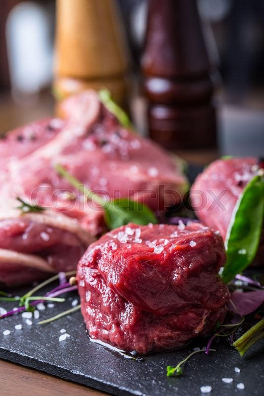 Stock image of 'Steak.Beef steak.Meat.Portioned meat.Raw fresh meat.Sirloin steak.T-Bone steak. Flank steak. Duck breast. Vegetable decoration. Portioned meat prepared for processing in a restaurant or hotel kitchen.'