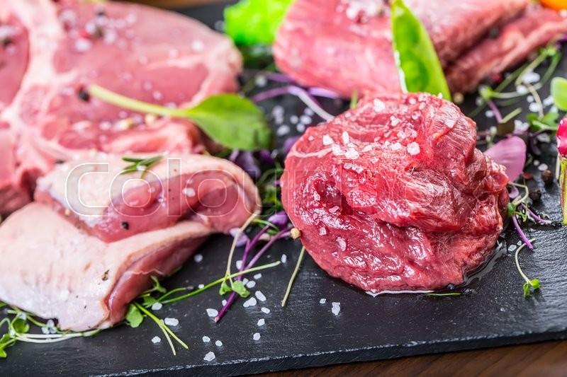 Steak.Beef steak.Meat.Portioned meat.Raw fresh meat.Sirloin steak.T-Bone steak. Flank steak. Duck breast. Vegetable decoration. Portioned meat prepared for processing in a restaurant or hotel kitchen, stock photo