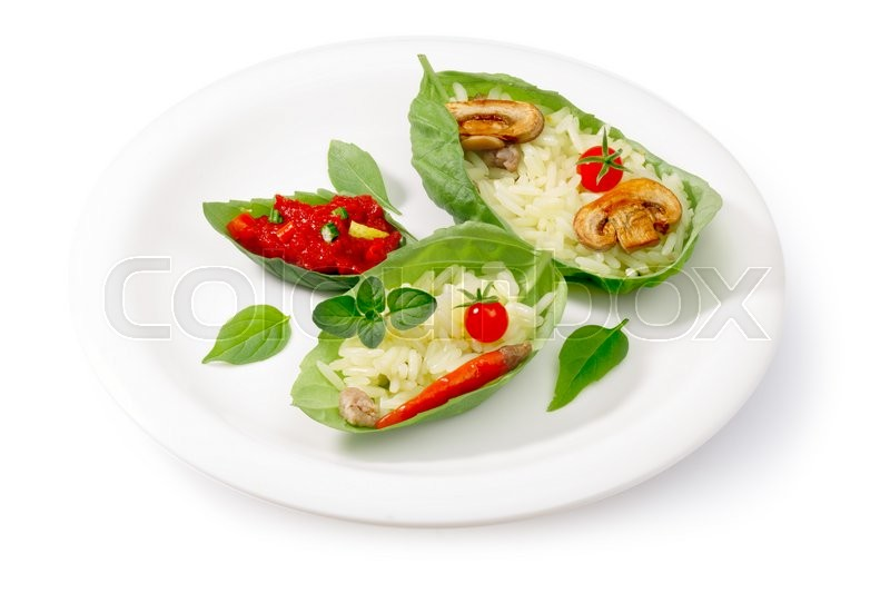 Stock image of 'Rice (risotto) served into lettuce leaf basil leaves. Clipping path, infinite depth of field'