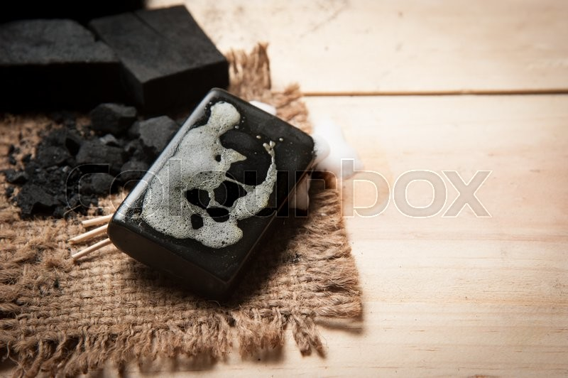 Stock image of 'Block of natural carbon soap and Black charcoal'