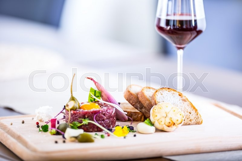 Stock image of 'Raw beef .Tasty Steak tartare. Classic steak tartare on wooden board. Ingredients: Raw beef meat salt pepper egg garlic chili herb decoration toast bread and cup of red wine.'