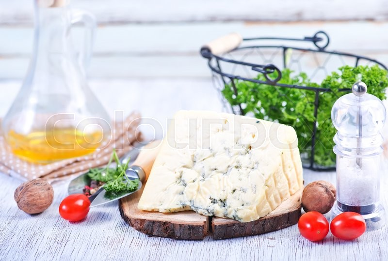 Stock image of 'cheese on board and on a table'