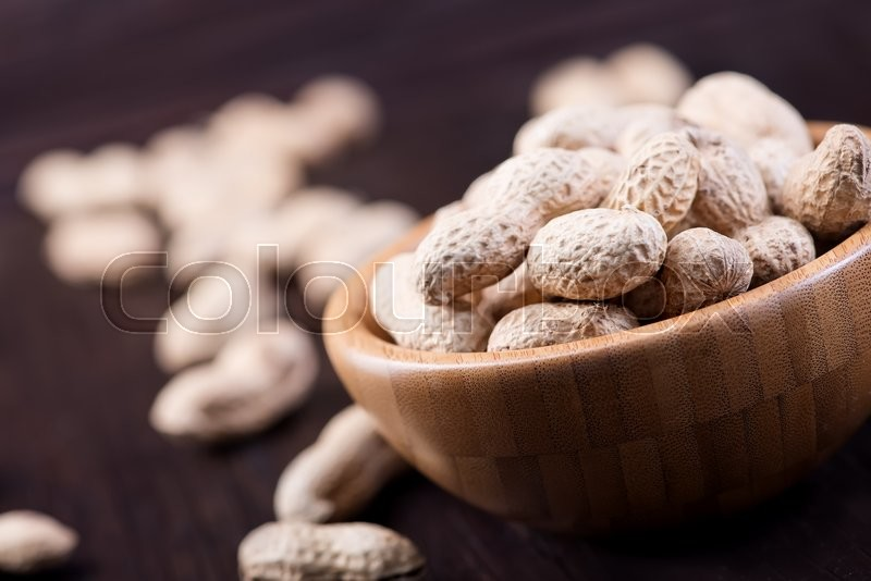 Stock image of 'peanuts in bowl and on a table'
