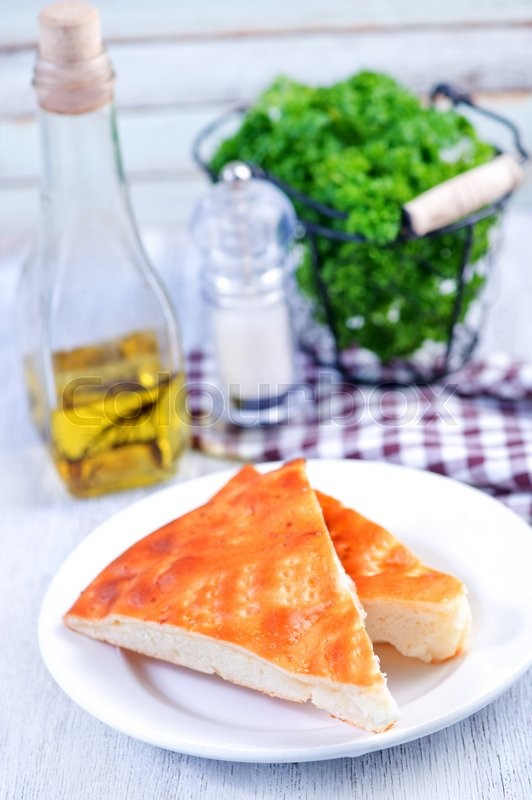 Stock image of 'pie with cheese on plate and on a table'