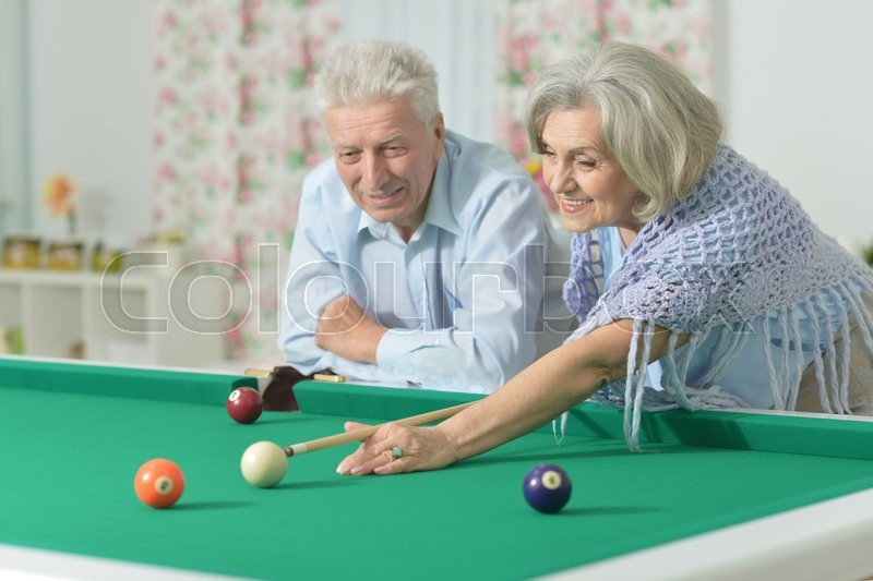 Stock image of 'Amusing old couple on vacation playing billiard'