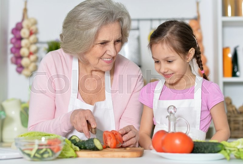 Stock image of 'Senior woman with granddaughter cooking in kitchen'