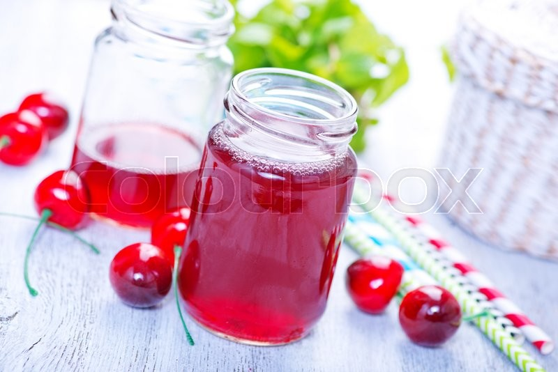 Stock image of 'cherry drink in glass and on a table'