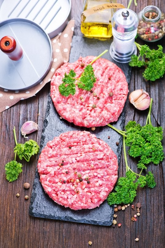 Stock image of 'raw burgers on board with salt and spice'