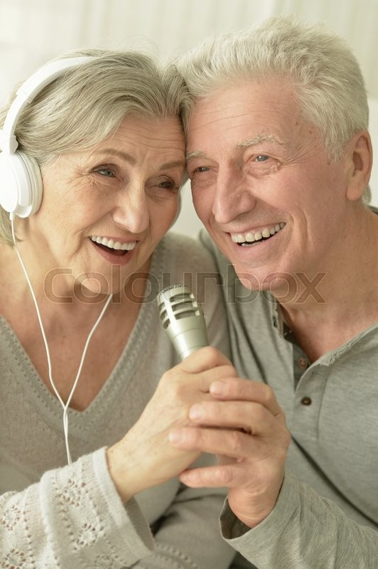 Stock image of 'Portrait of a senior couple with headphones and microphone'